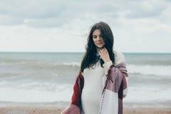 Jeune belle femme pragnant posant près de la mer à la plage Photo libre de droits