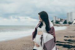 Jeune belle femme pragnant posant près de la mer à la plage Image libre de droits