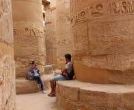 Jeune belle femme prenant des photos entre les colonnes du hall hypostyle du temple de Karnaks à Louxor, Egypte Photographie stock