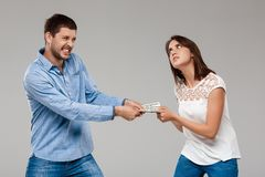 Jeune belle femme prenant l'argent de l'homme au-dessus du fond gris Images stock