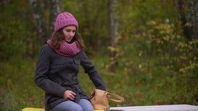 Jeune belle femme prenant le téléphone portable de son sac, se reposant sur le banc en parc d'automne Femme utilisant son smartph banque de vidéos