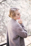 Jeune belle femme près des arbres dans la fleur au printemps Photos stock