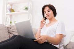 Jeune belle femme réfléchie avec le téléphone et l'ordinateur portable sur le sofa Photographie stock libre de droits