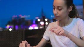 Jeune belle femme regardant le menu dans le restaurant et faisant l'ordre pour la datation d'événement de déjeuner de dîner banque de vidéos