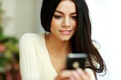 Jeune belle femme réfléchie à l'aide du smartphone Image libre de droits