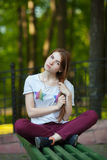 Jeune belle femme rousse dans la chemise rouge d'espadrilles de jeans se reposant sur le banc touchant son fond trouble de Forest Images stock
