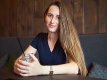 Jeune belle femme rousse heureuse de portrait avec des taches de rousseur buvant du café en café à la pause-café photo stock