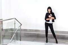 Jeune belle femme sérieuse de brune avec un carnet habillé dans une position noire de costume contre le mur blanc dans a images libres de droits