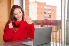 Jeune belle femme s'asseyant avec la tasse de la boisson et communiquer par l'ordinateur portable photographie stock libre de droits