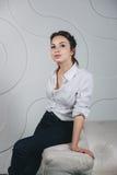 Jeune belle femme s'asseyant contre le blanc Images libres de droits