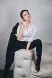 Jeune belle femme s'asseyant contre le blanc Photos libres de droits