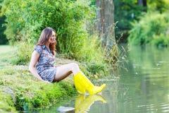Jeune belle femme s'asseyant dans des canots en caoutchouc jaunes de pluie par un r Photos libres de droits