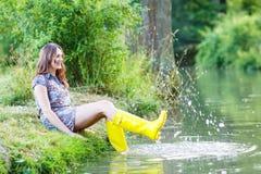Jeune belle femme s'asseyant dans des canots en caoutchouc jaunes de pluie par un r Image stock
