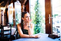 Jeune belle femme s'asseyant dans la barre ou le restaurant Image stock