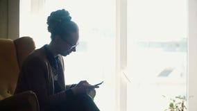 Jeune belle femme s'asseyant dans la chaise jaune près de la fenêtre et à l'aide du smartphone, causant dans l'Internet banque de vidéos