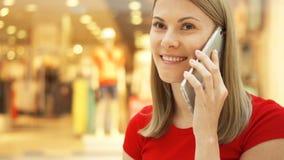 Jeune belle femme s'asseyant dans le sourire de centre commercial Utilisant son smartphone, parlant avec des amis clips vidéos