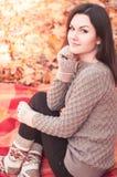 Jeune belle femme s'asseyant en parc d'automne Image libre de droits