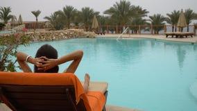 Jeune belle femme s'asseyant sur des canapés du soleil par la piscine à l'hôtel banque de vidéos