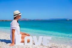 Jeune belle femme s'asseyant sur la plage avec Images libres de droits