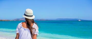 Jeune belle femme s'asseyant sur la plage avec Image libre de droits