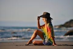 Jeune belle femme s'asseyant sur la plage en été Images stock