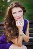 Jeune belle femme s'asseyant sur le banc en parc photographie stock libre de droits