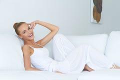 Jeune belle femme s'asseyant sur le divan Image stock