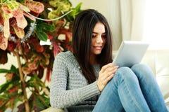 Jeune belle femme s'asseyant sur le fauteuil avec la tablette Image libre de droits