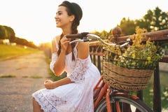 Jeune belle femme s'asseyant sur sa bicyclette avec des fleurs au soleil photos libres de droits