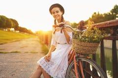 Jeune belle femme s'asseyant sur sa bicyclette avec des fleurs au soleil images stock