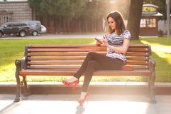 Jeune belle femme s'asseyant sur un banc et introduisant un message dessus Photographie stock
