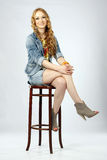 Jeune belle femme s'asseyant sur un tabouret Image stock