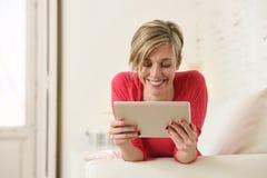 Jeune belle femme 30s heureuse souriant utilisant le divan numérique de salon de protection de comprimé à la maison Photos libres de droits