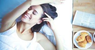 Jeune belle femme se situant dans le lit à la maison Photos stock