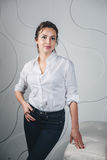 Jeune belle femme se tenant contre le blanc Photographie stock libre de droits