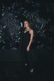 Jeune belle femme se tenant contre le noir Photographie stock libre de droits