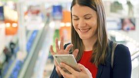 Jeune belle femme se tenant dans le sourire de centre commercial Utilisant son smartphone, parlant avec des amis clips vidéos