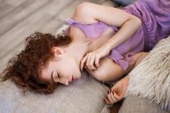 Jeune belle femme se trouvant sur le lit, les beaux cheveux rouges, la relaxation et le concept de relaxation photographie stock libre de droits