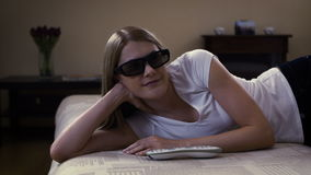 Jeune belle femme se trouvant sur un divan Les commutateurs à la TV futée, met dessus 3d-glasses et observe le film 3d banque de vidéos