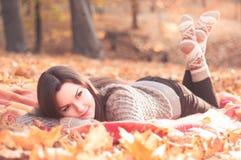 Jeune belle femme se trouvant sur une couverture en parc d'automne Photo stock