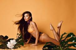 Jeune belle femme sexy avec les feuilles de prise douce parfaite de peau et les fleurs tropicales d'orchid?e images stock