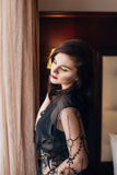 Jeune belle femme sexy dans une robe de chambre noire de dentelle posant dans une chambre Image libre de droits