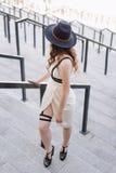 Jeune belle femme sexy portant l'équipement à la mode, la robe blanche, le chapeau noir et le swordbelt de cuir Brune à cheveux l Photo stock