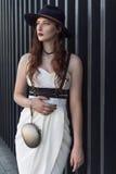 Jeune belle femme sexy portant l'équipement à la mode, la robe blanche, le chapeau noir et le swordbelt de cuir Brune à cheveux l Image libre de droits