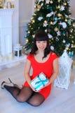 Jeune belle femme souriant à l'appareil-photo et s'asseyant avec le cadeau dedans Image libre de droits