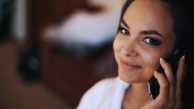 Jeune belle femme souriant et parlant au téléphone portable dans la chambre banque de vidéos