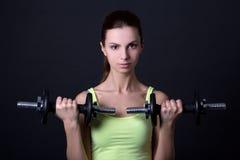 Jeune belle femme sportive avec des haltères au-dessus de gris Photo libre de droits