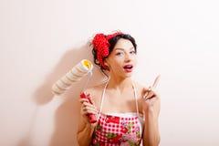 Jeune belle femme stupéfaite tenant le rouleau de peinture Photographie stock libre de droits