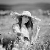 Jeune belle femme sur le gisement de céréale avec des pavots en été Images libres de droits