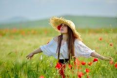 Jeune belle femme sur le gisement de céréale avec des pavots en été Photos stock